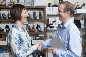Businessman Shaking Hands With Shoe Store Retailer